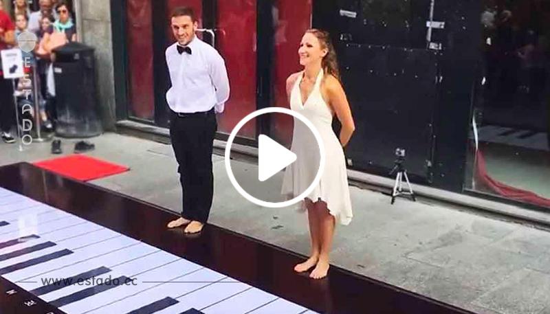 Una pareja toca una canción clásica en un piano gigante con los pies, y este buenísimo